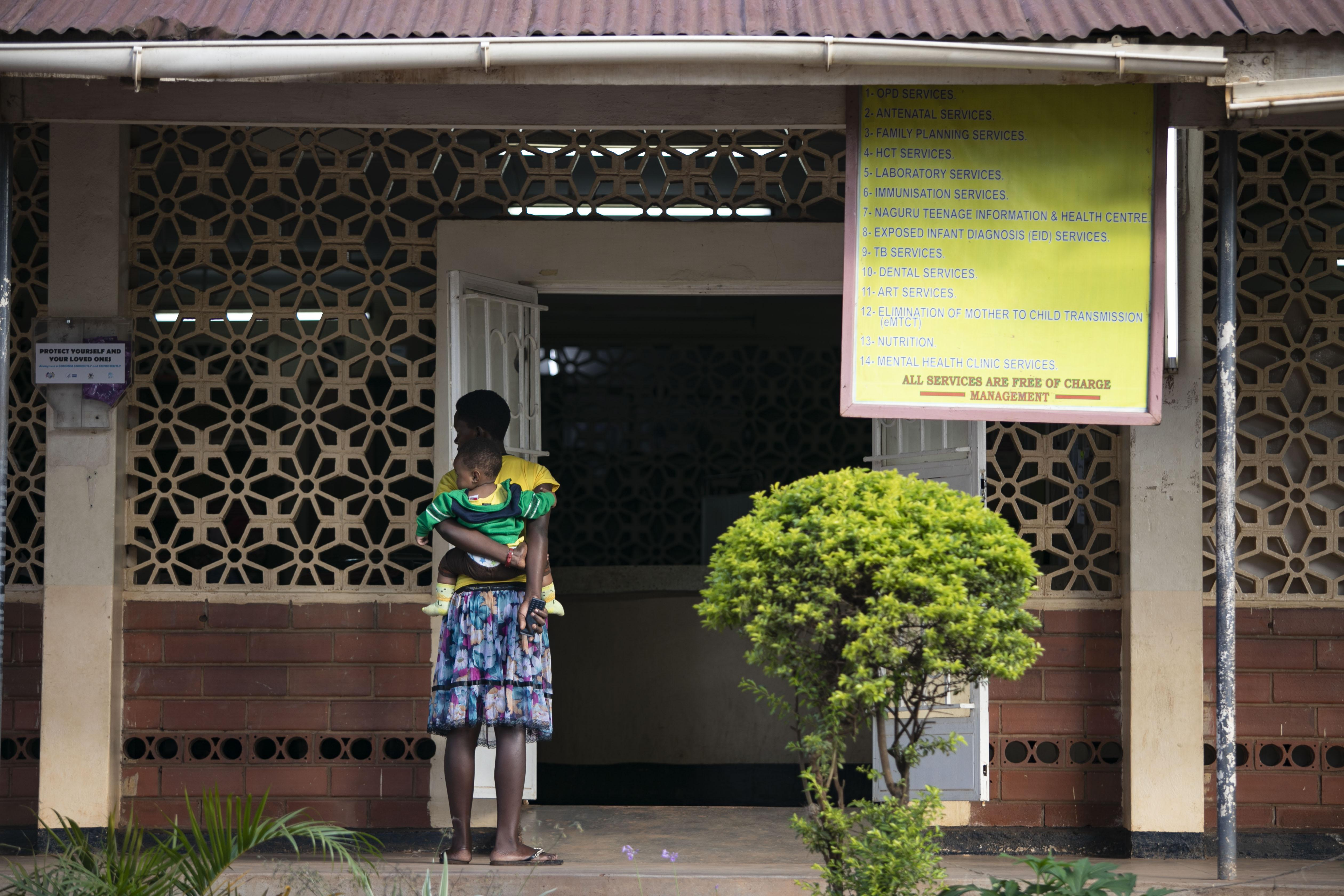 Woman with baby on her back and standing in front of a Ugandan facility
