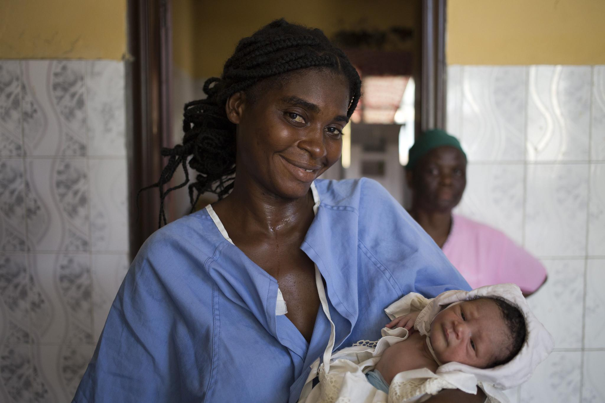 Female doctor holding new born baby